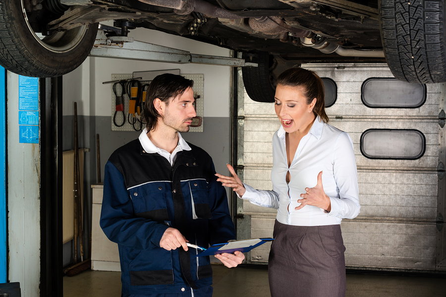 Car mechanic with attractive but angry female customer going through maintenance checklist in garage - apparently the efforts are overpriced since the woman is screaming at the mechanic.