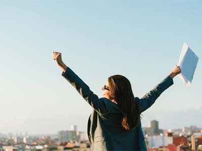 Business Woman Celebrating Success Towards City Skyline