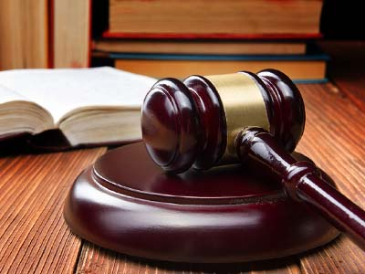 Law book with wooden judges gavel on table in a courtroom or law