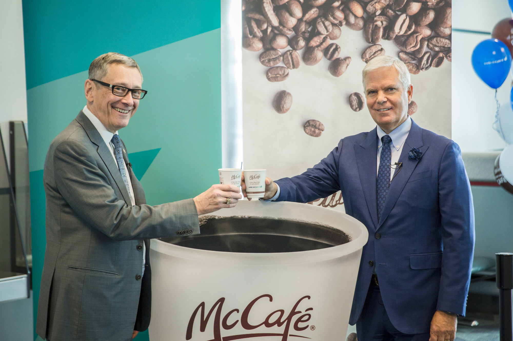 Gregg Saretsky, WestJet President and CEO, and John Betts, McDonald's Canada, President and CEO, toast to honour the inaugural flight of McCafé Premium Roast coffee being served on WestJet flights. Both executives were on hand to greet guests at the gate Monday, November 21. (CNW Group/WestJet)