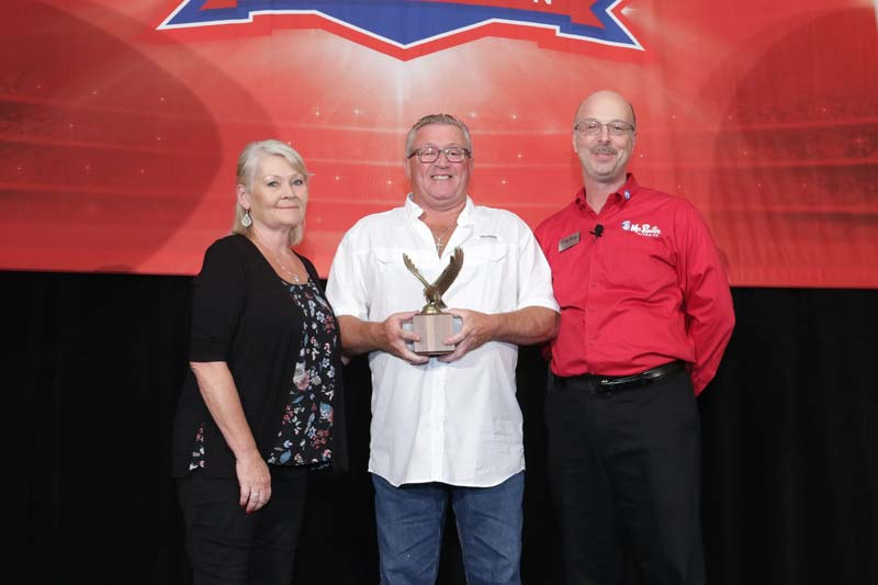 Pamela and Derek Moreland accept the Mr. Rooter Plumbing franchisee of the year award from company president Doyle James.